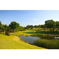The par-4 17th hole at Vaaler Creek Golf Club features a small, elevated green set over a water hazard.