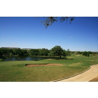 The sixth hole on the Lakes nine at Hill Country Golf Club wraps around a pond.