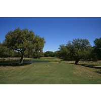 From the tee, the eighth green on the Oaks nine at Hill Country Golf Club is tucked between two oaks and over a pond.