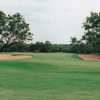 A view of a green flanked by sand traps and trees at Quicksand Golf Course.