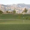 A view of green with mountains in background at Shadow Hills Golf Course