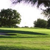 A sunny view of green protected by bunker at Bentwood Country Club