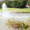A view of green with water fountain in foreground at Bentwood Country Club