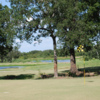 A view of a green with water in background at Oak Trail Golf Course.