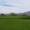 A view of a green with mountains in the distance at Painted Dunes Desert Golf Course.