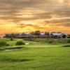 A sunset view of the clubhouse and a green at The Golf Club of Texas.